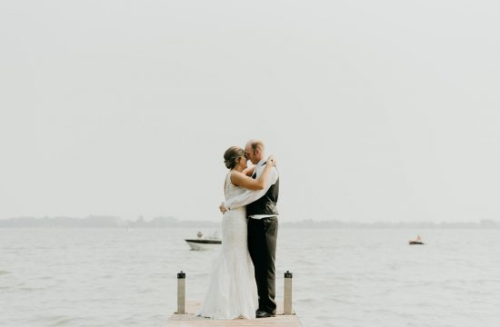 Lakeside photo of bride and groom on a dock with the lake in the background
