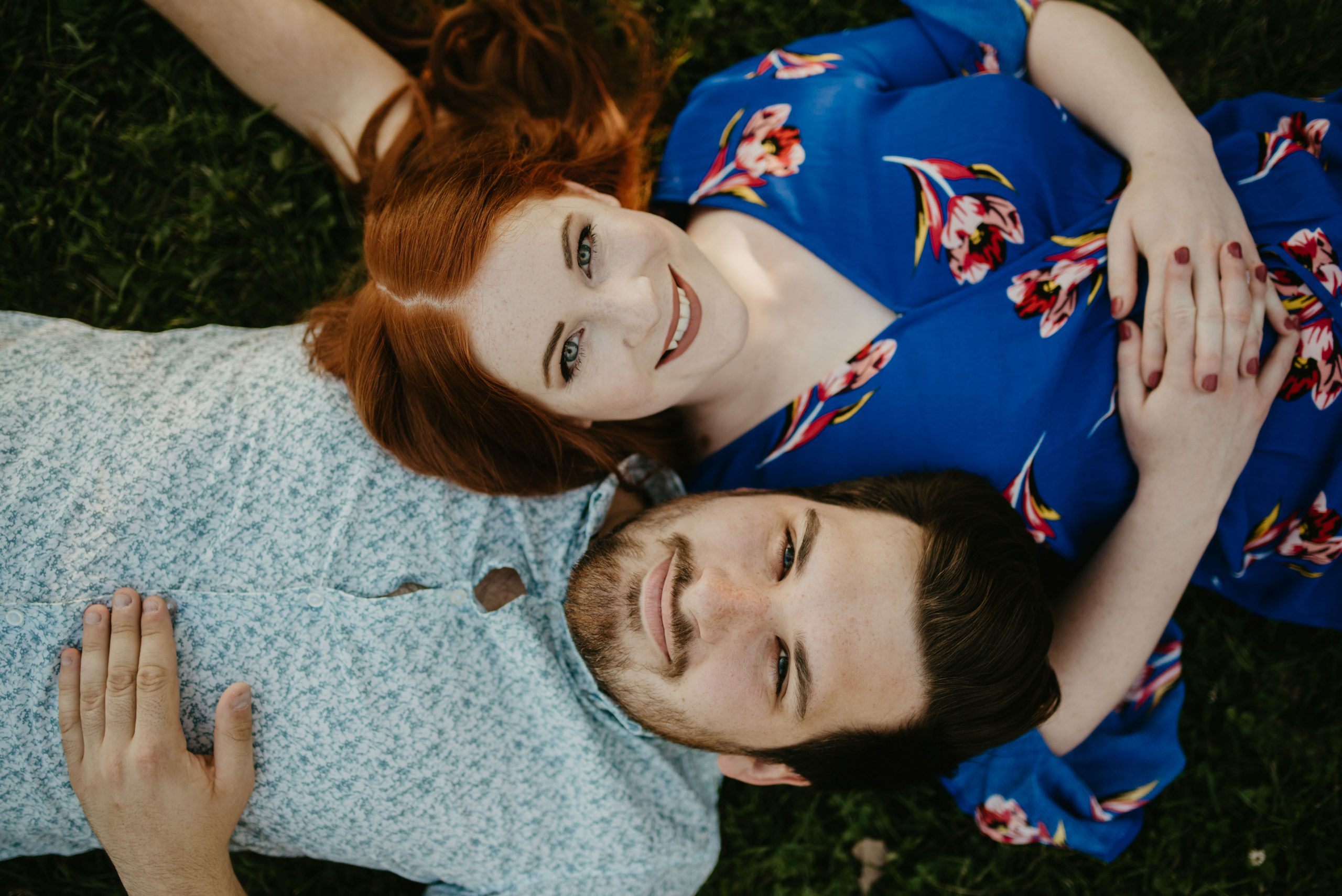 engaged couple laying down in the grass engagement photos minneapolis