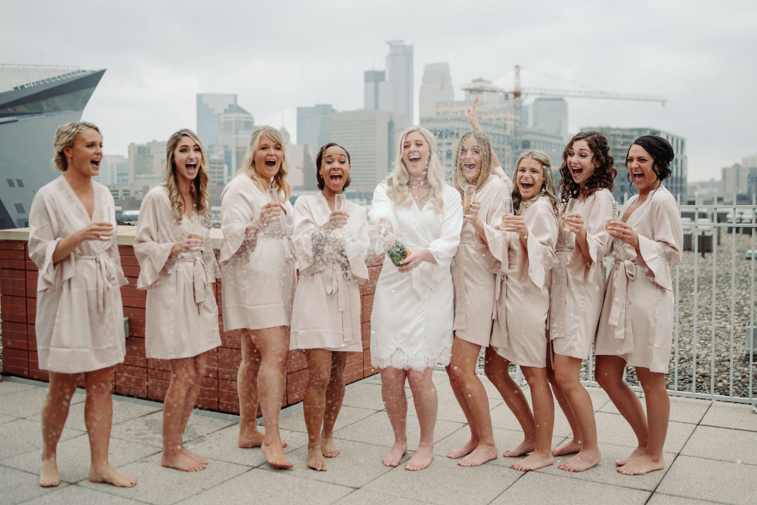 bridal party getting ready popping champagne on a rooftop minneapolis minnesota