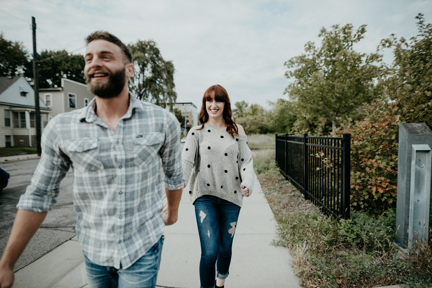 engaged couple walking together laughing