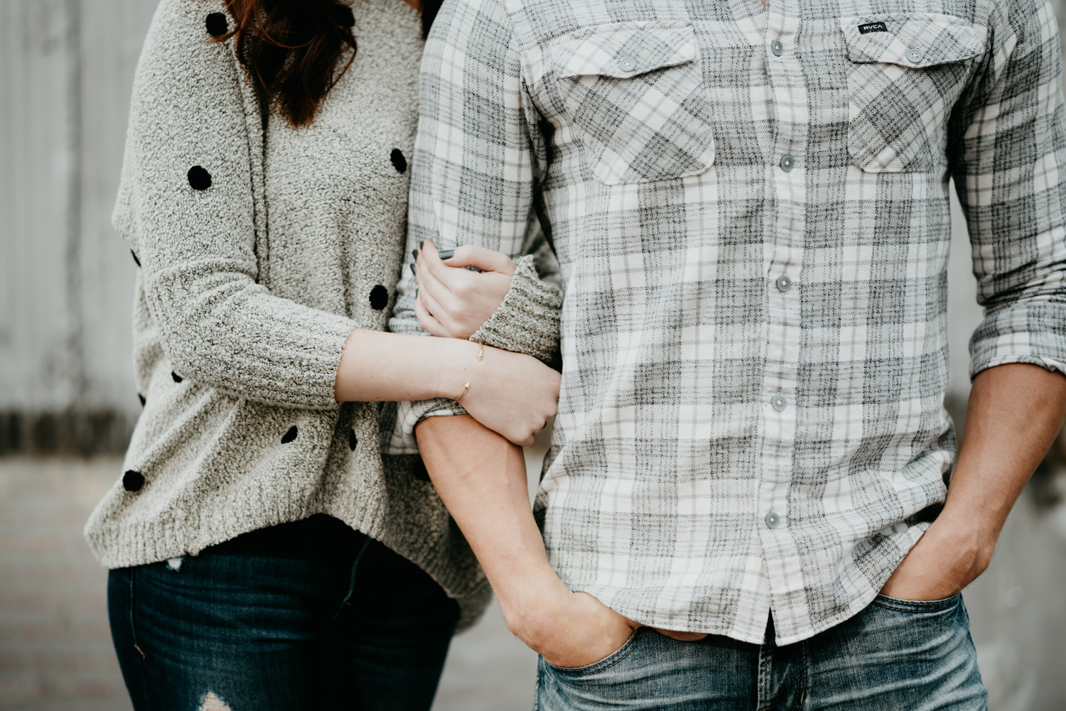 engaged couple holding each other hands in pockets