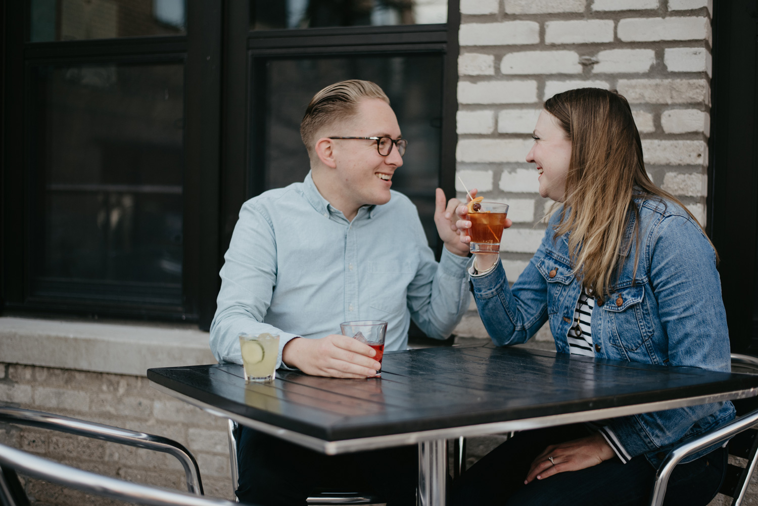 engaged couple having a drink and laughing at each other