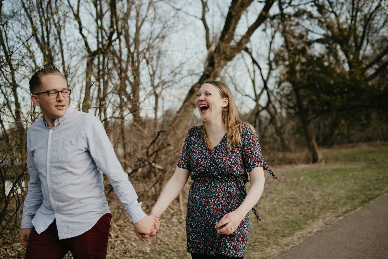 engaged couple laughing and walking by lake