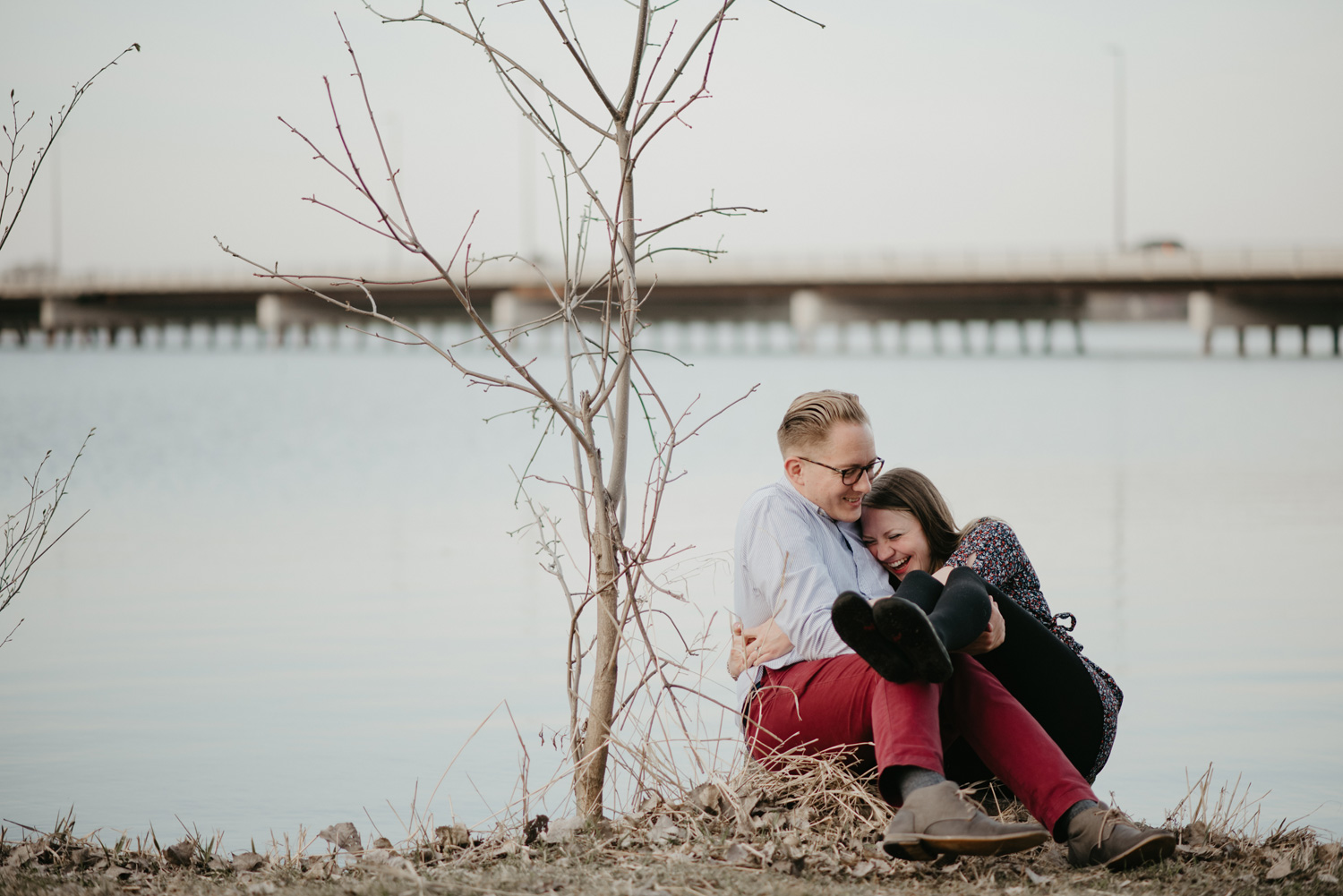 engaged couple laughing and cuddling by lake