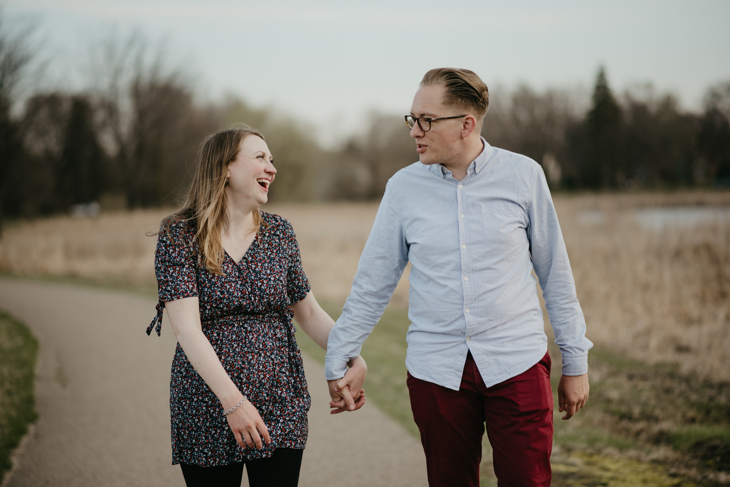 engaged couple holding hands and laughing