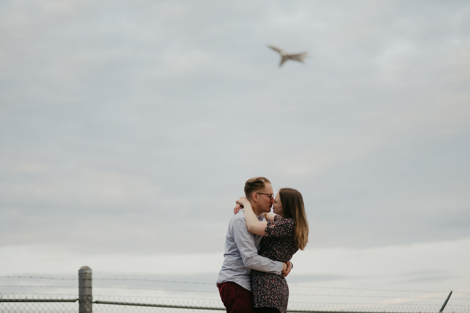 engaged couple kissing in front of plane