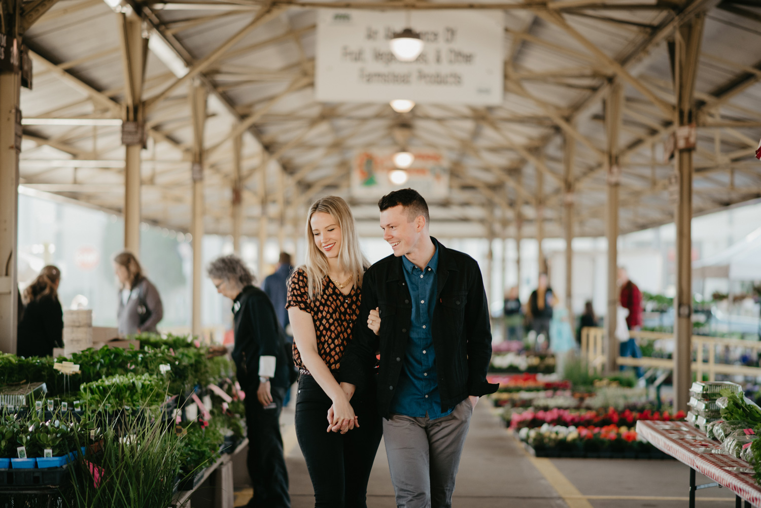 engaged happy couple walking and laughing at farmers market