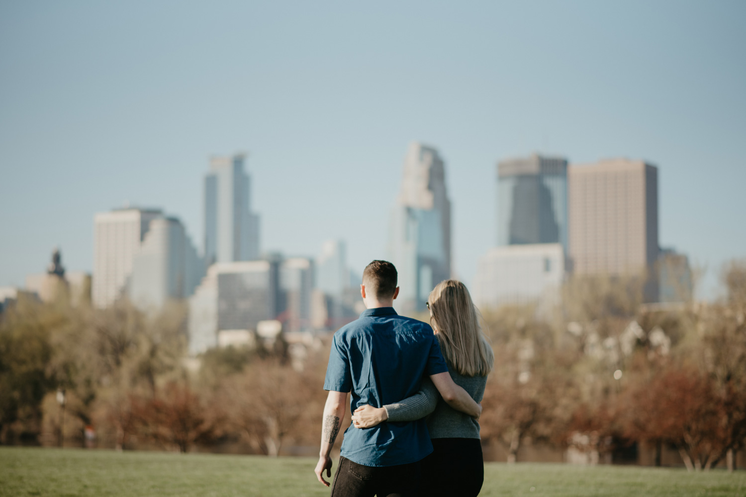 engaged happy couple hugging in front of skyline