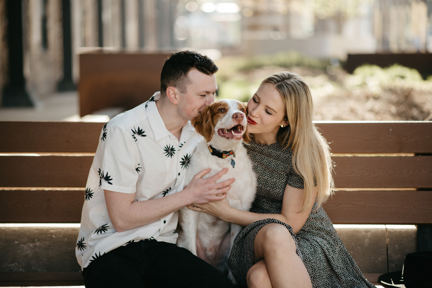 engaged happy couple kissing dog