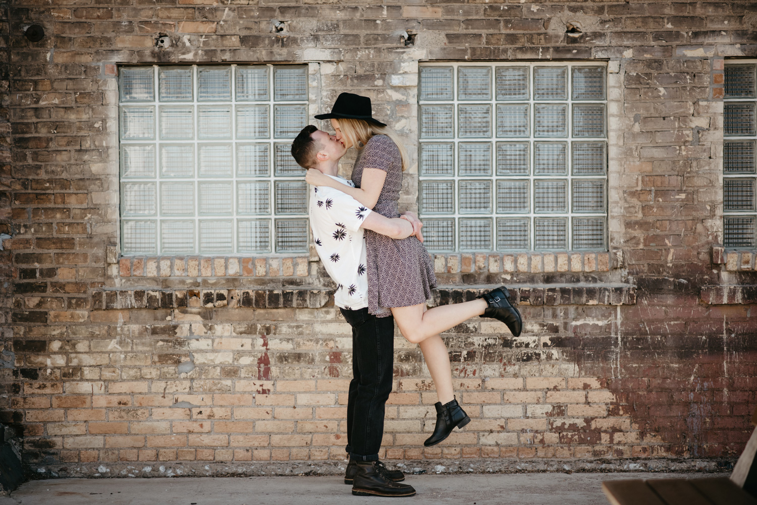 engaged happy couple kissing in front of rustic brick wall