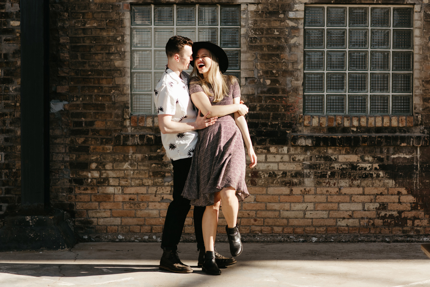 engaged happy couple posing in front of rustic brick wall