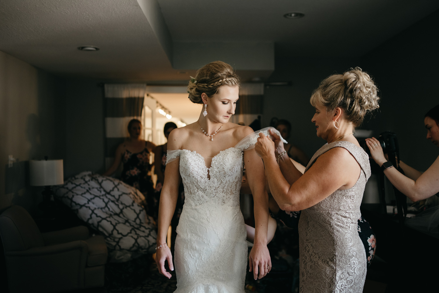 Mom helping bride put on her wedding dress