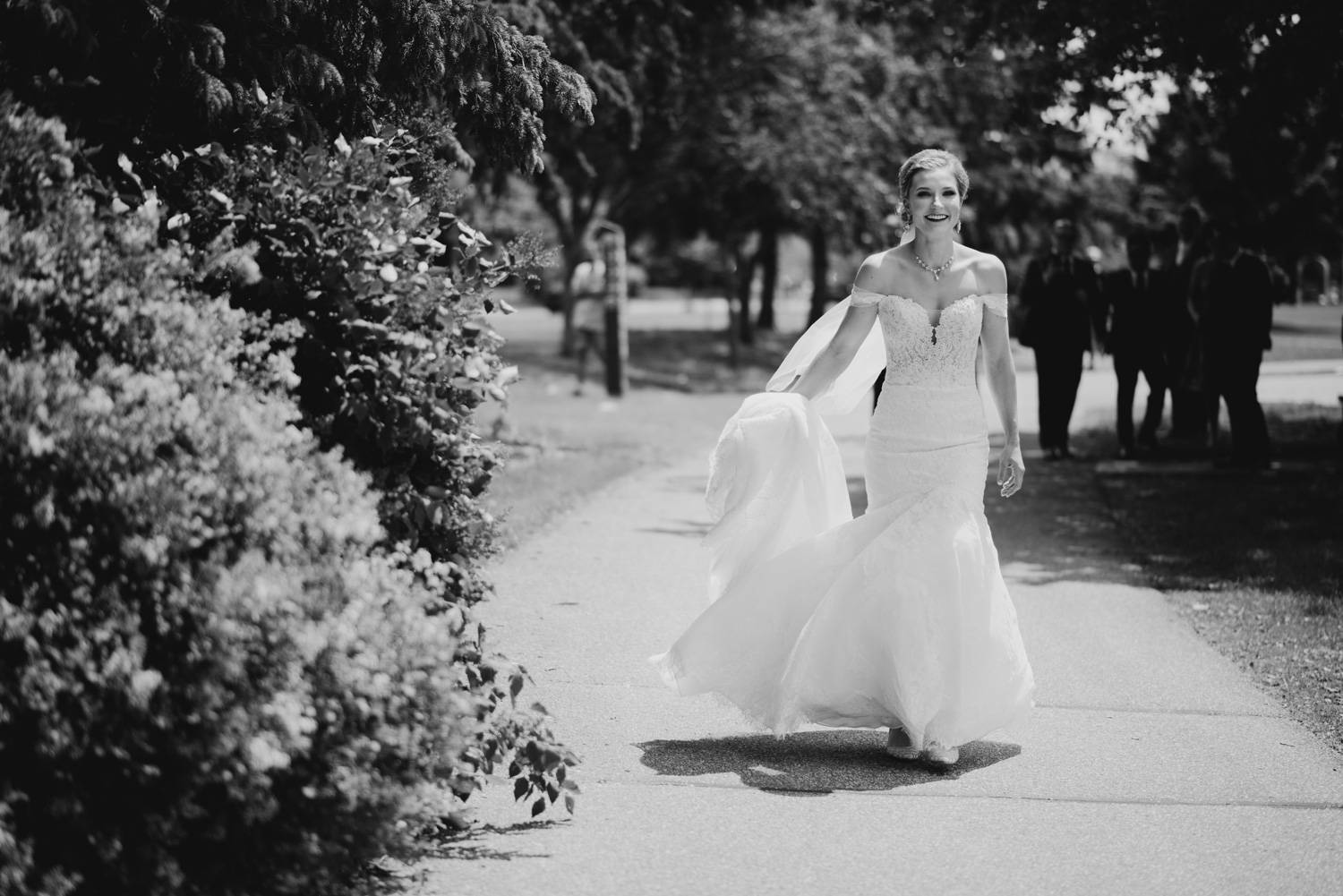 Bride walking towards groom on sidewalk