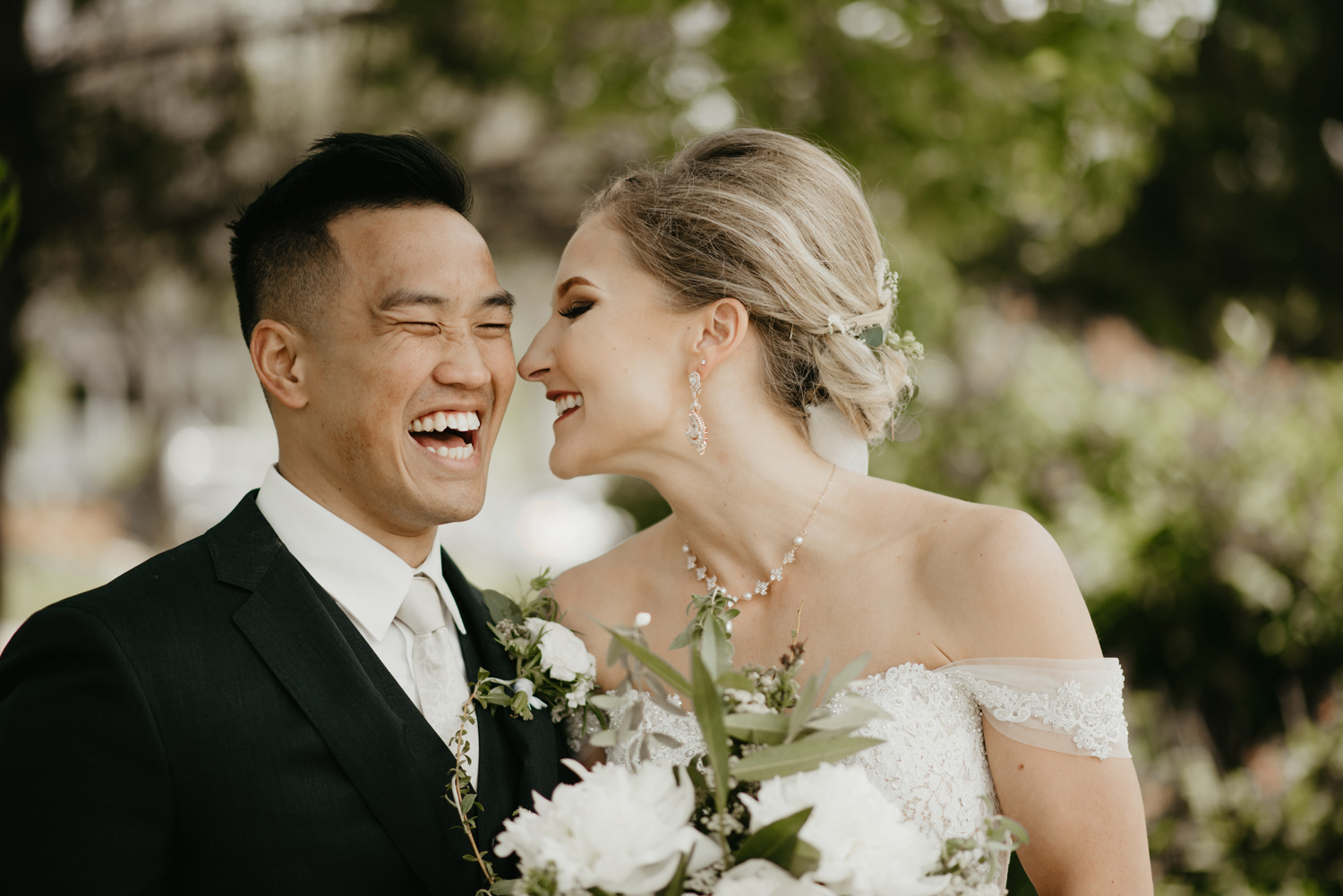 Bride and groom laughing together close up