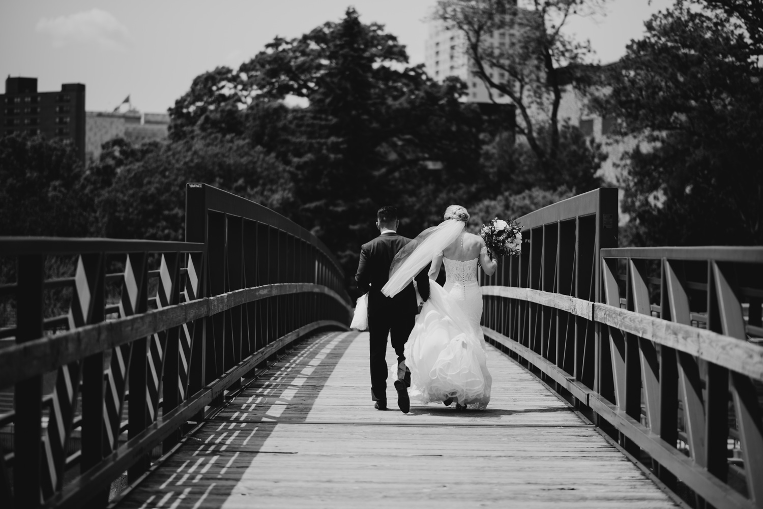 Bride and groom walking on bridge black and white