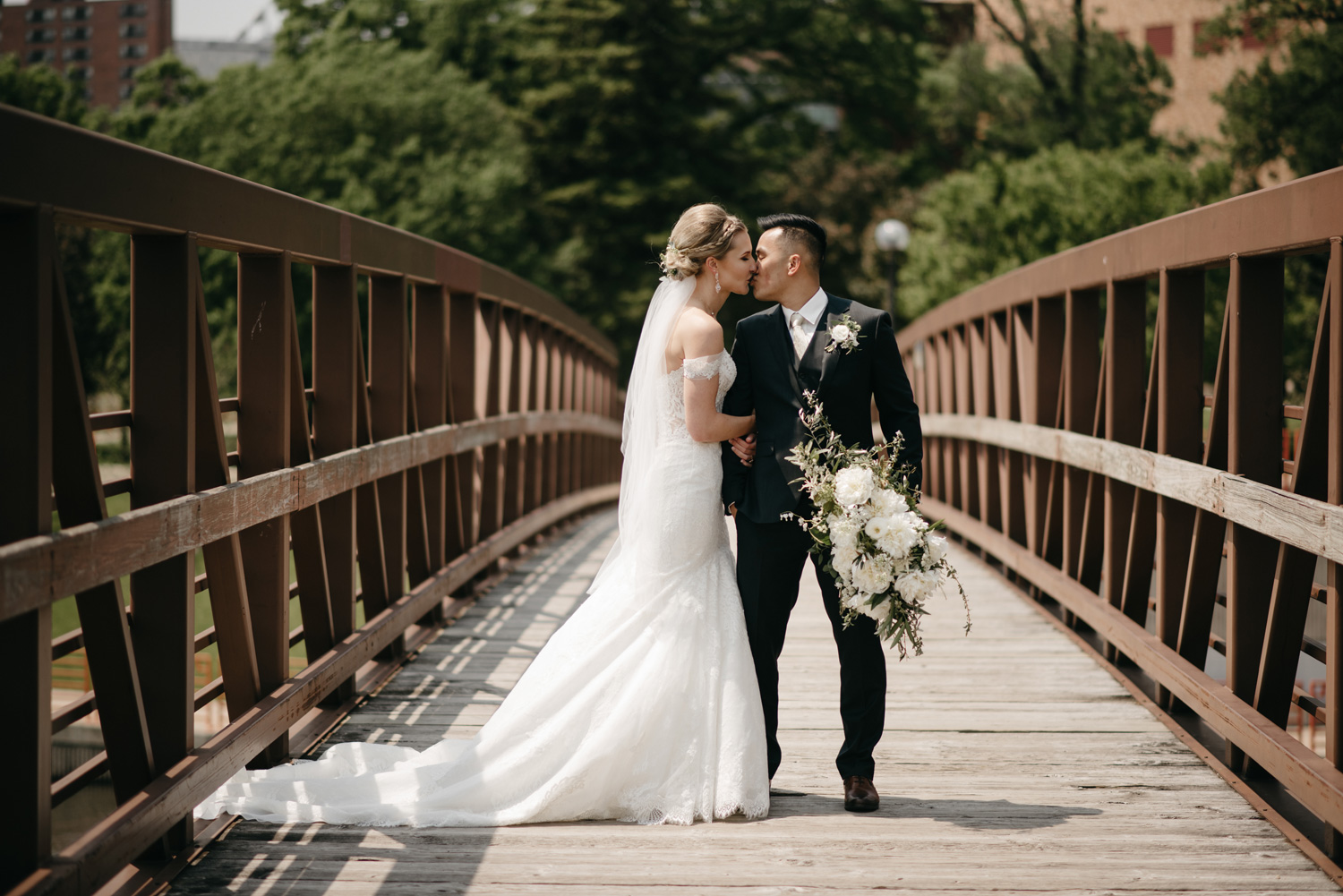 Bride and groom posing on bridge