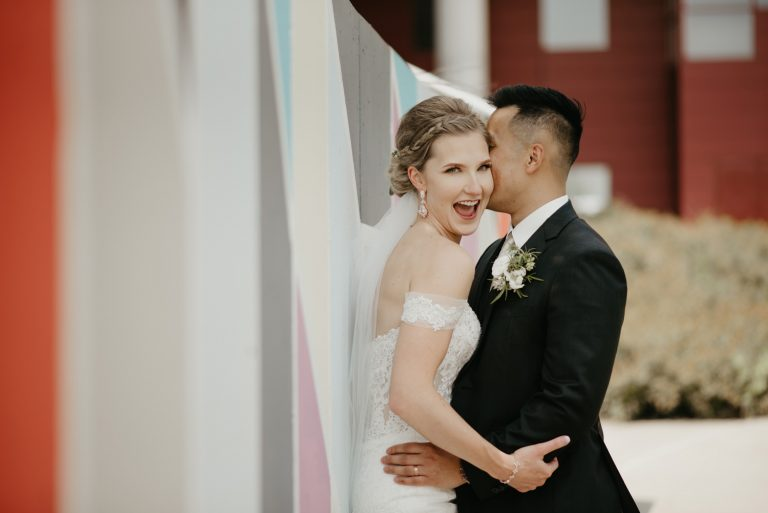 groom giving bride a kiss on the cheek