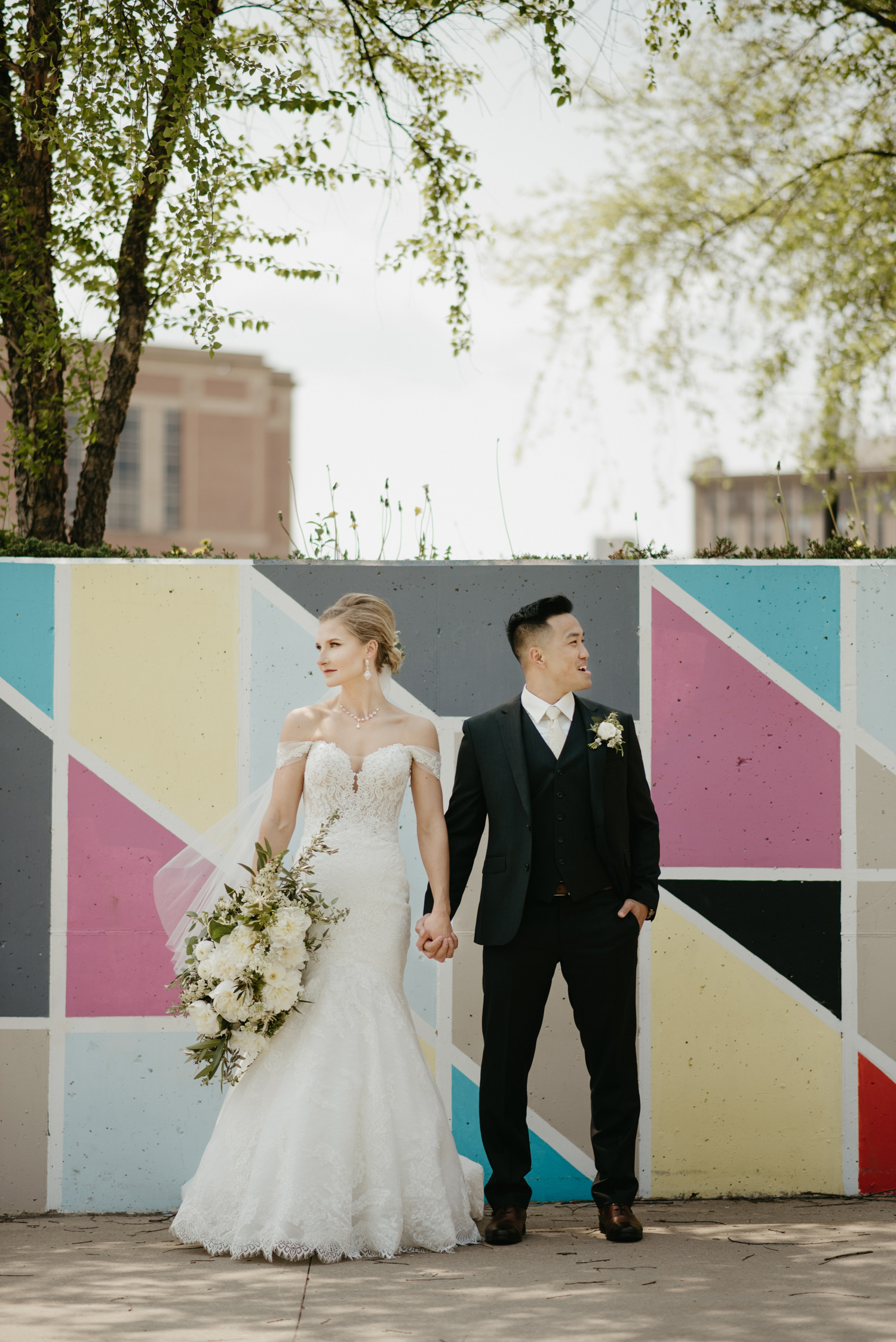 Bride and groom posing in front of multicolored wall