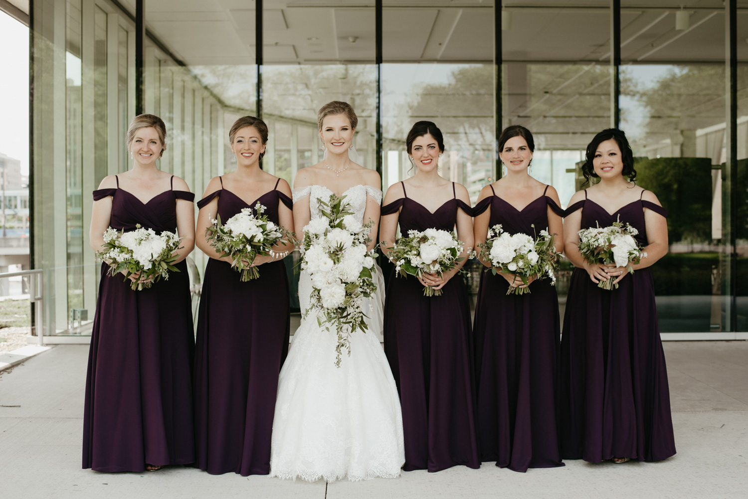 Bride and bridesmaids standing with floral in purple dresses