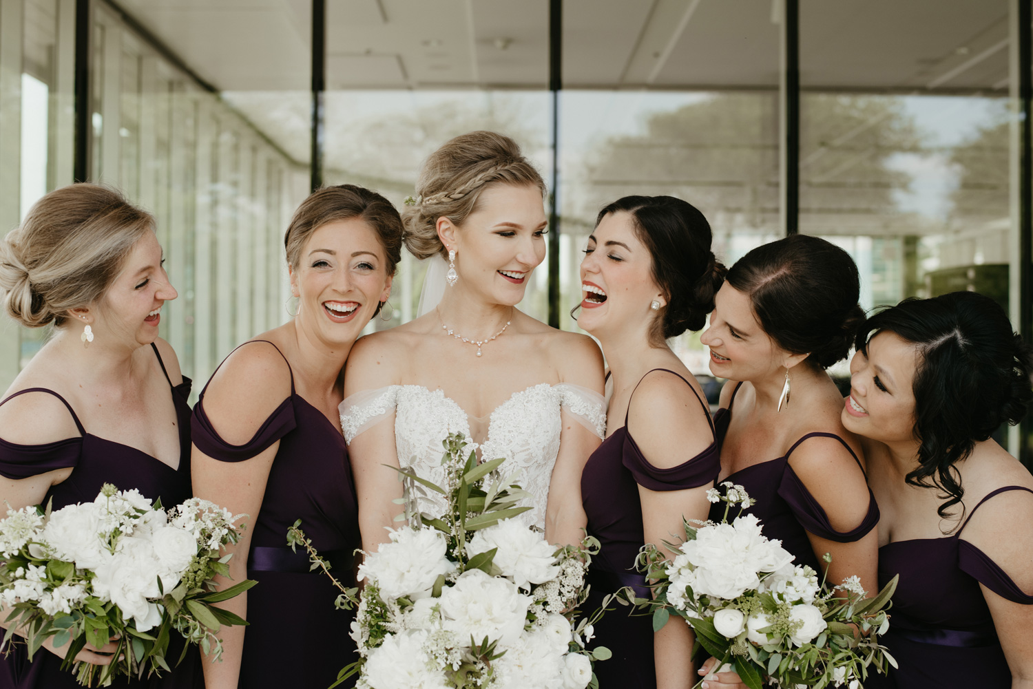 Bridal party and bride laughing at one another