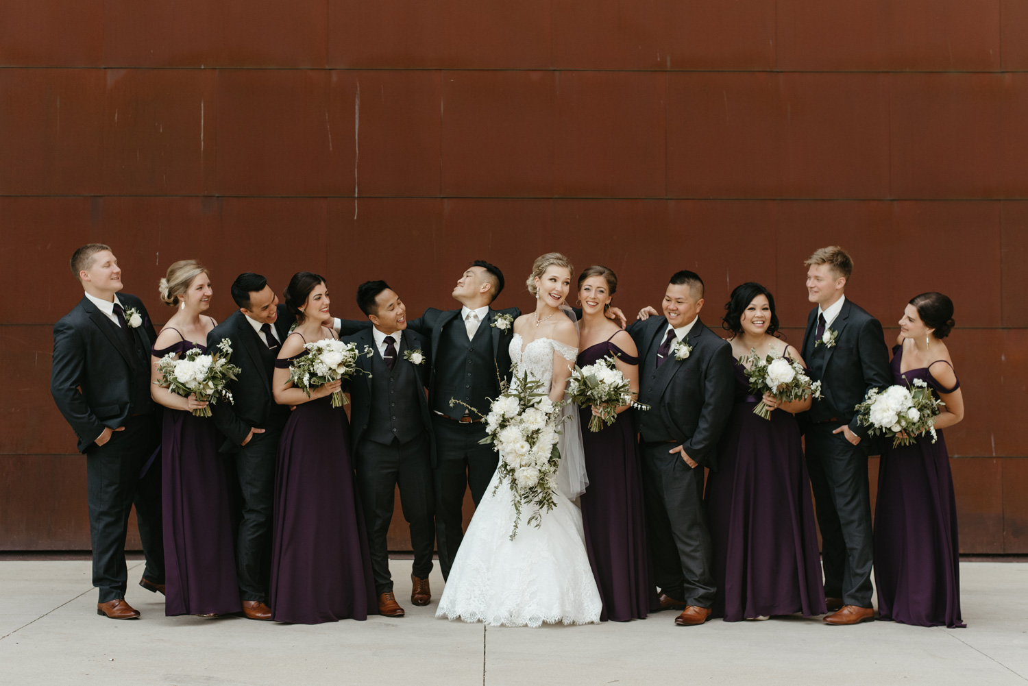 Portraits of wedding party in front of rusted wall