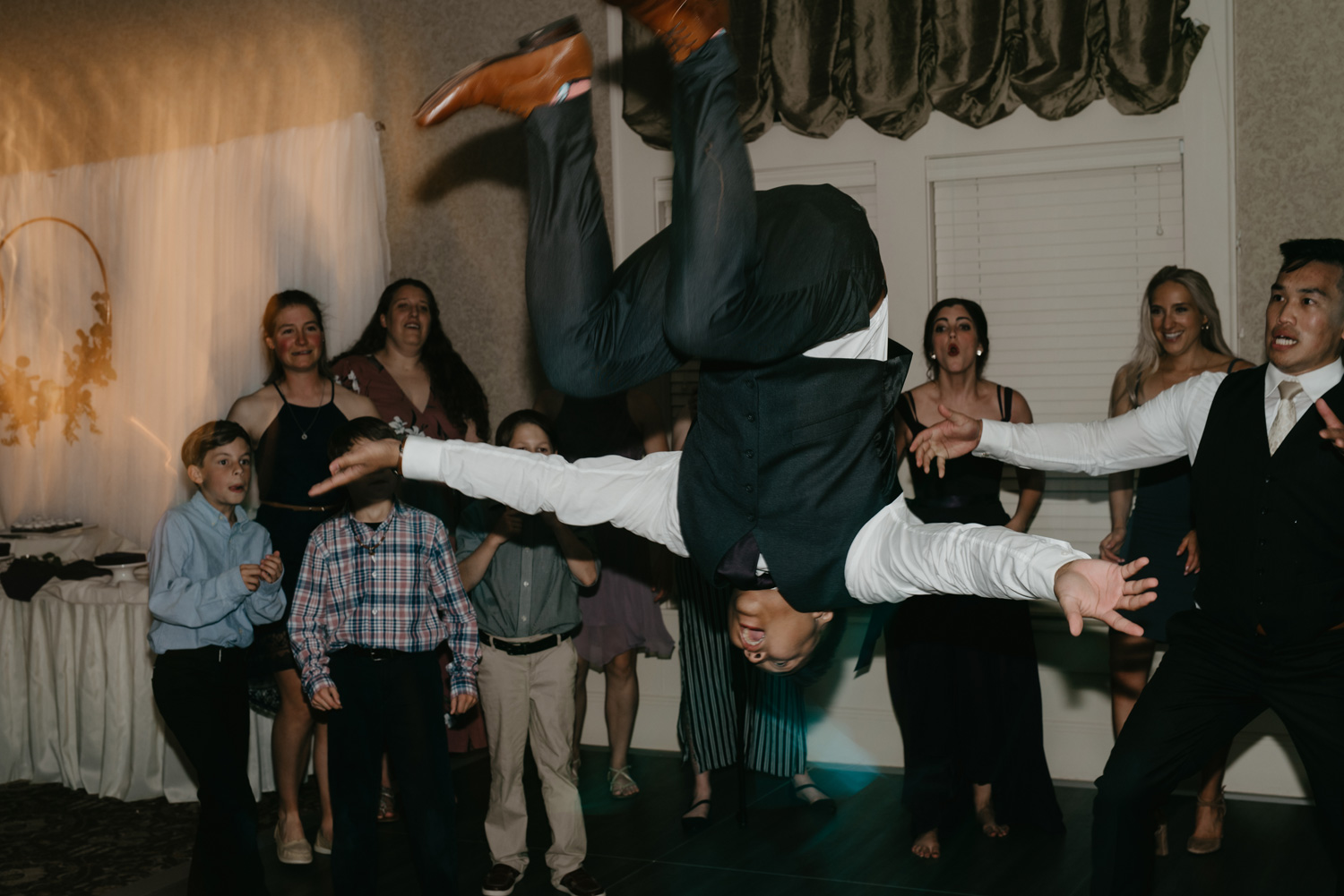 Guy doing backflip on wedding dancefloor