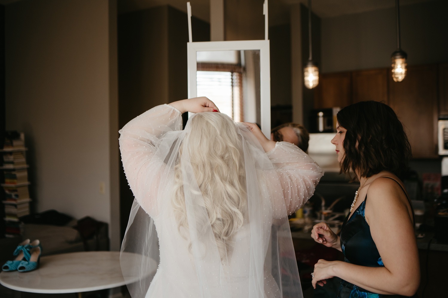 Bride putting on her veil from behind