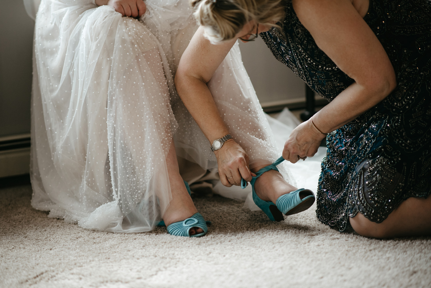 Bride's mom helping her put on blue suede shoes
