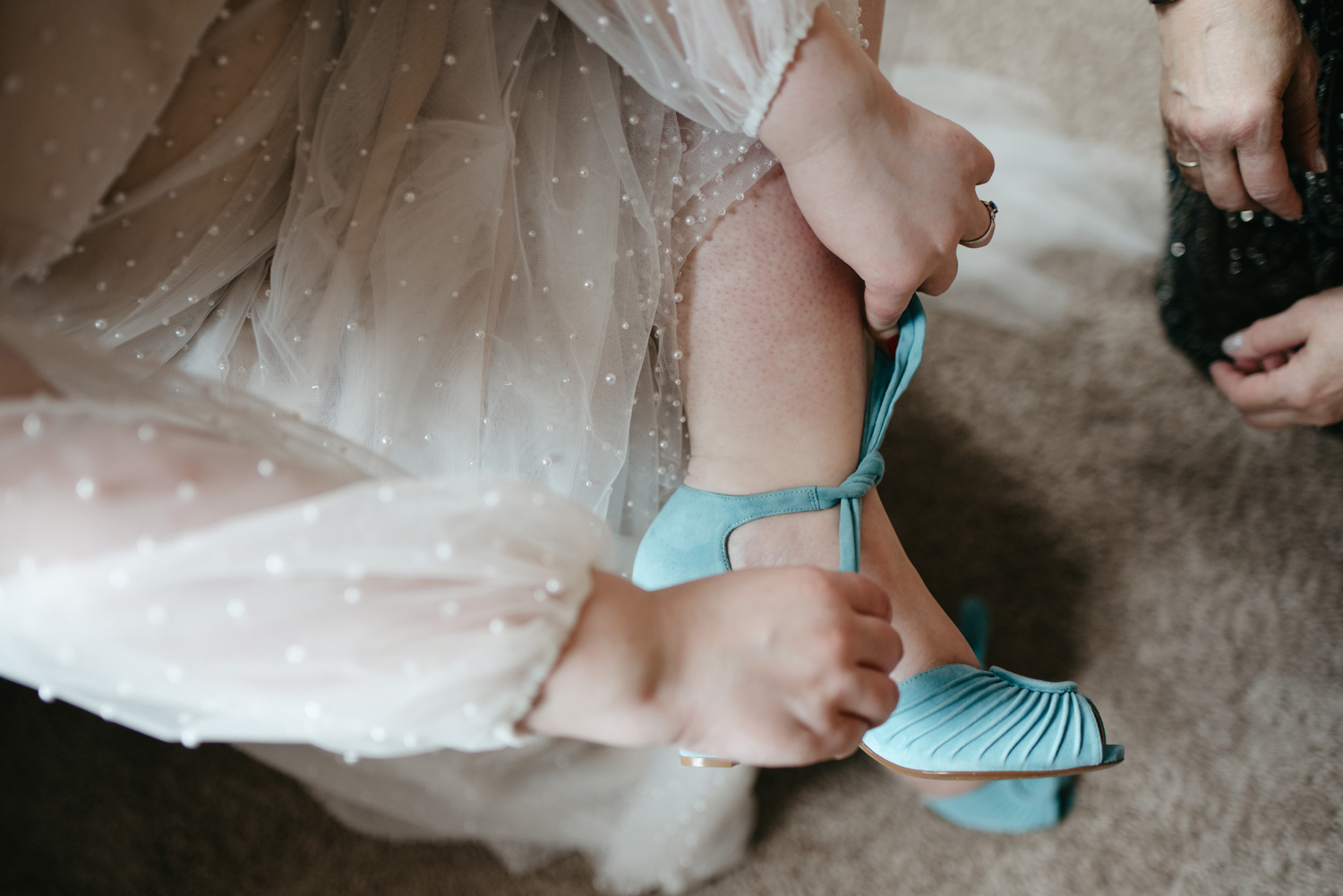 Bride putting on her blue suede shoes