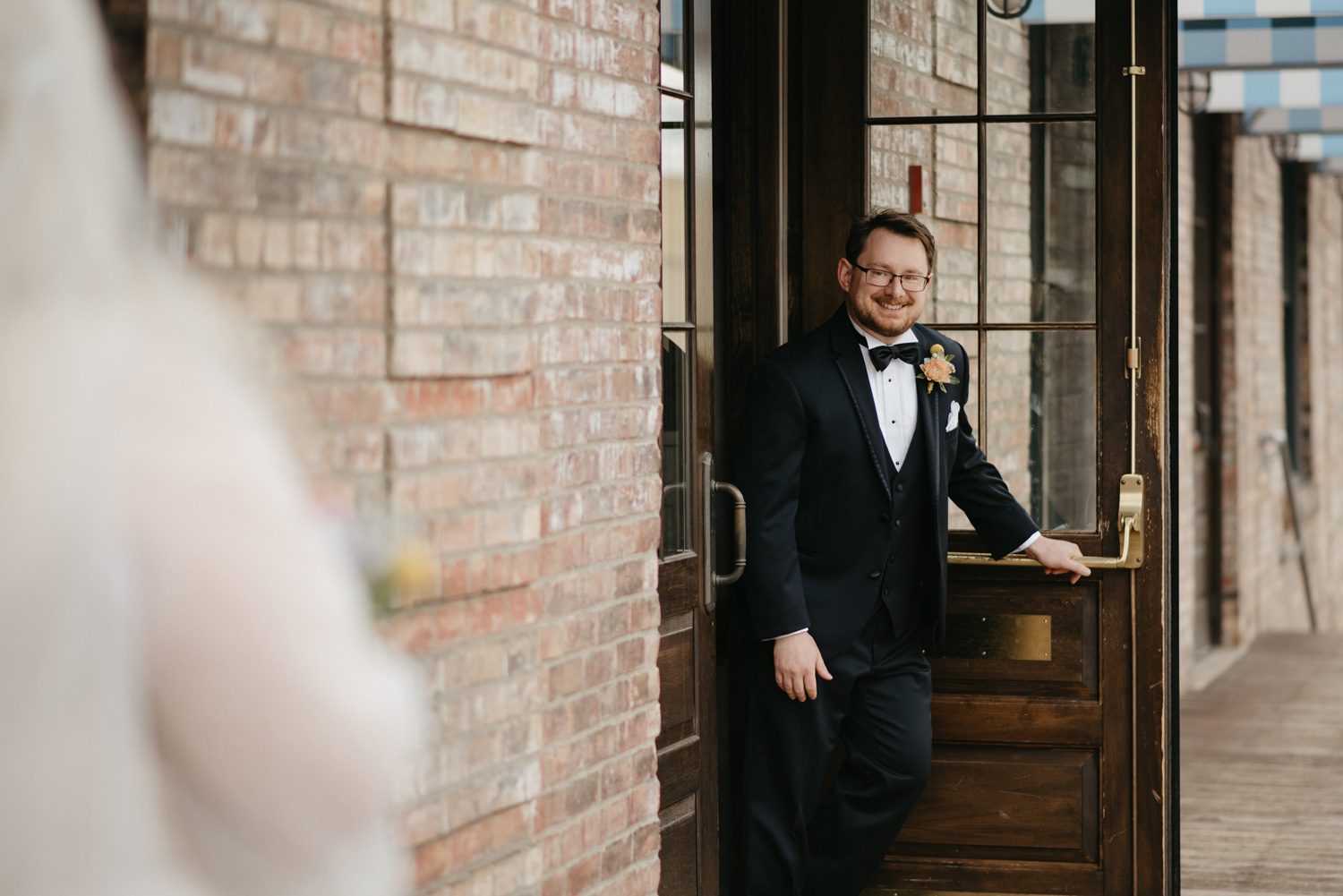 Groom coming out of venue for first look with surprised face