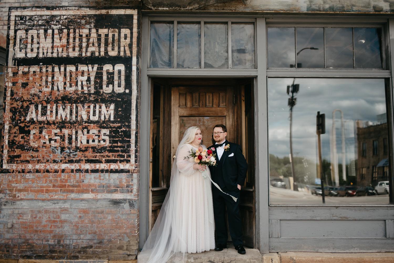 Bride and Groom posing in an industrial doorway in Minneapolis