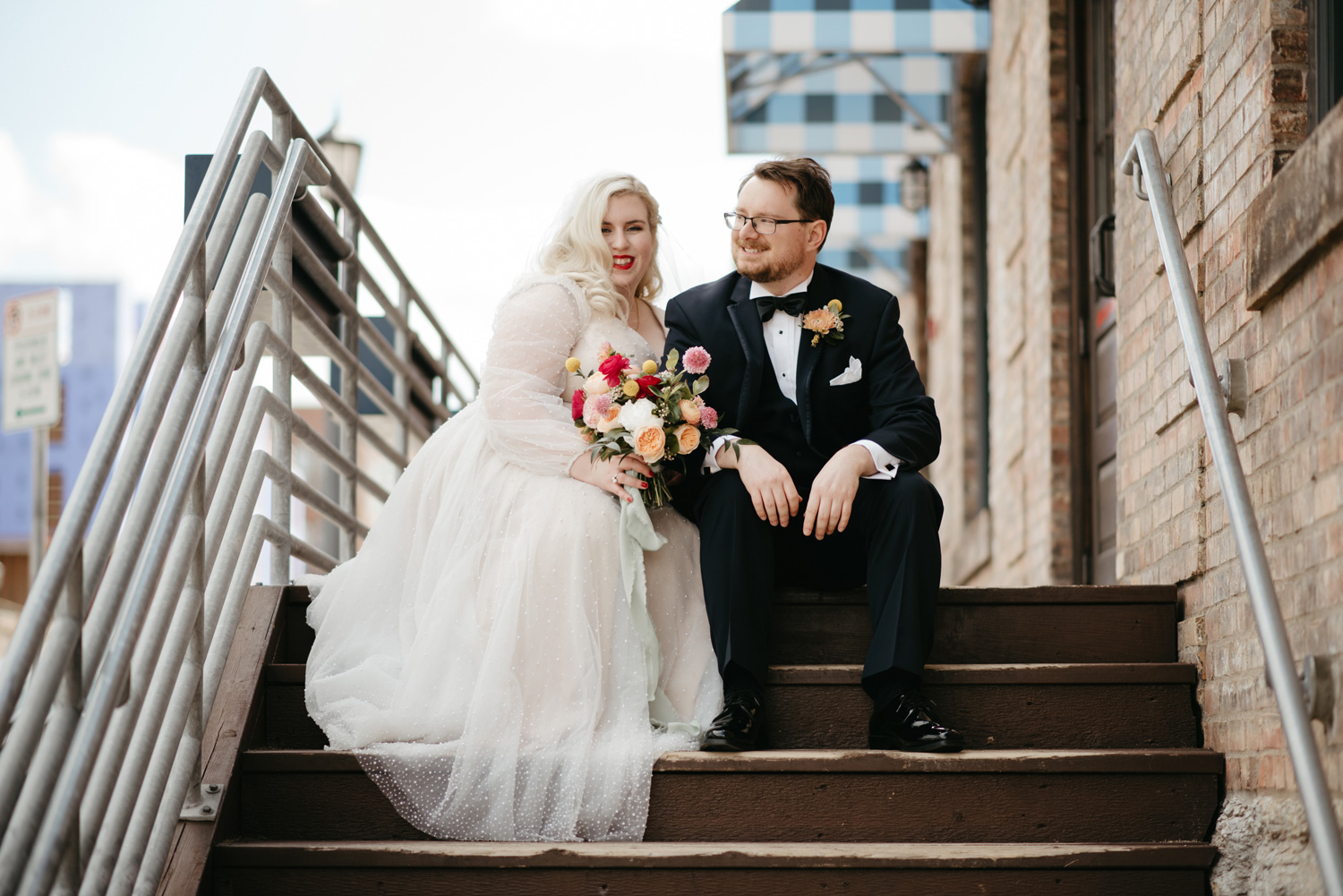 Bride and Groom sitting on outdoor steps leading up to venue