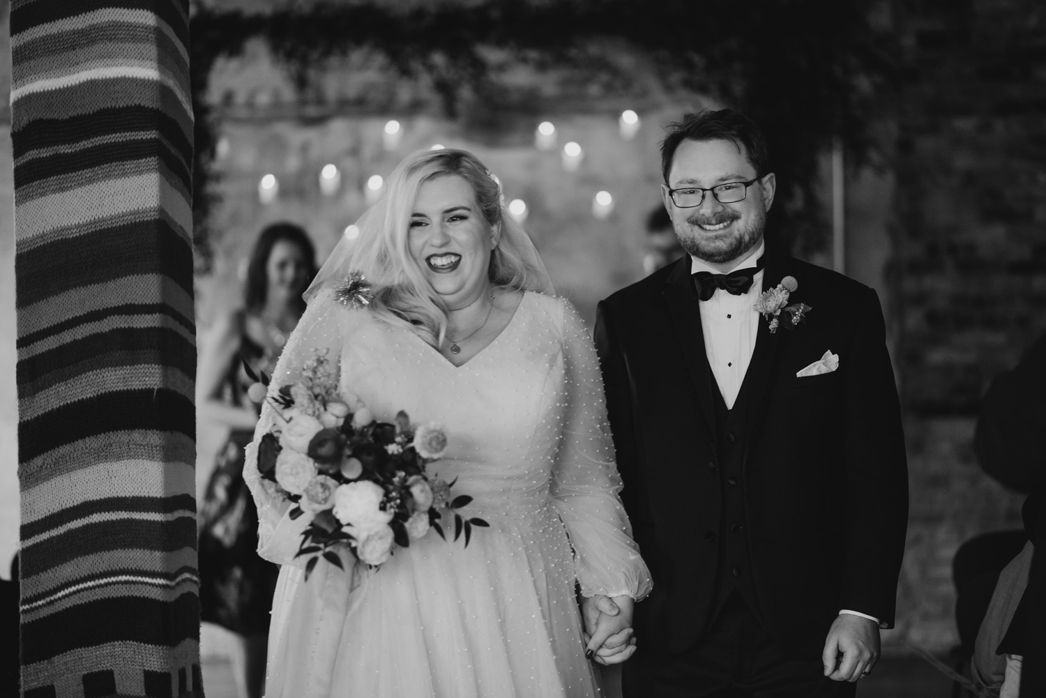 Black and white image of bride and groom walking down aisle after announced as husband and wife with big smiles
