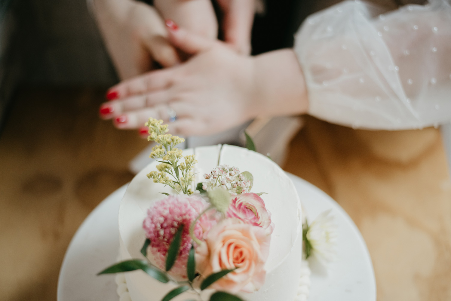 Close up photo of bride and groom's hands as they cut the cake