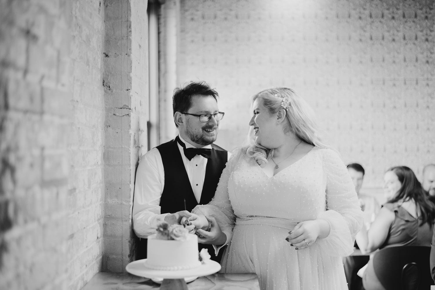 Black and white image of the bride and groom cutting their wedding cake at Bachelor Farmer, Minneapolis
