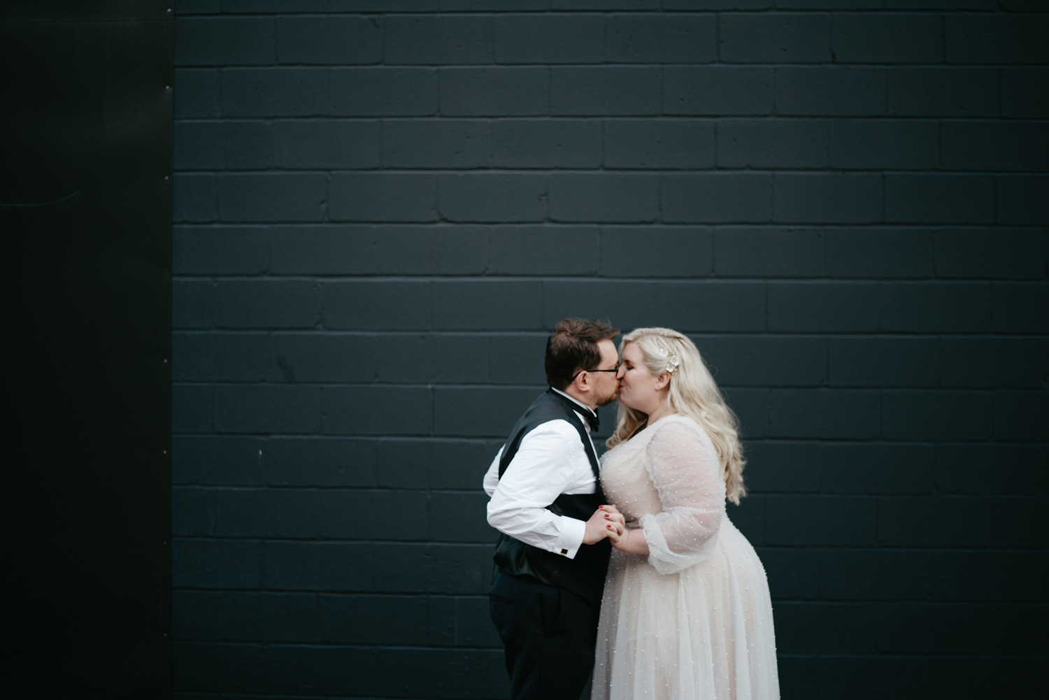 Bride and Groom in front of grey cinderblock wall in Minneapolis