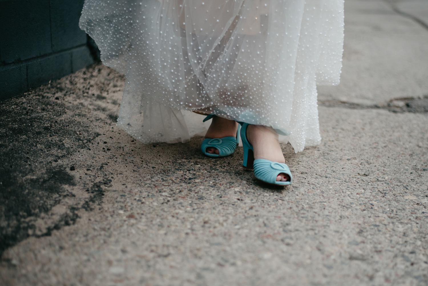 Up close photo of bride walking with blue suede shoes