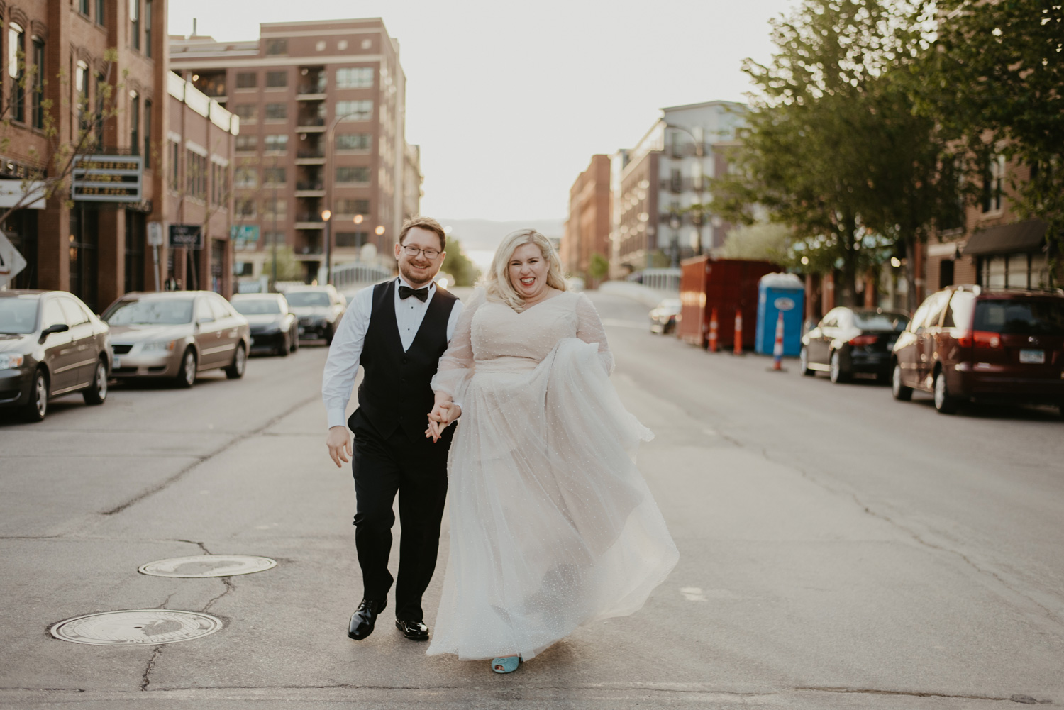 Bride and groom twirling in the middle of Minneapolis street during sunset