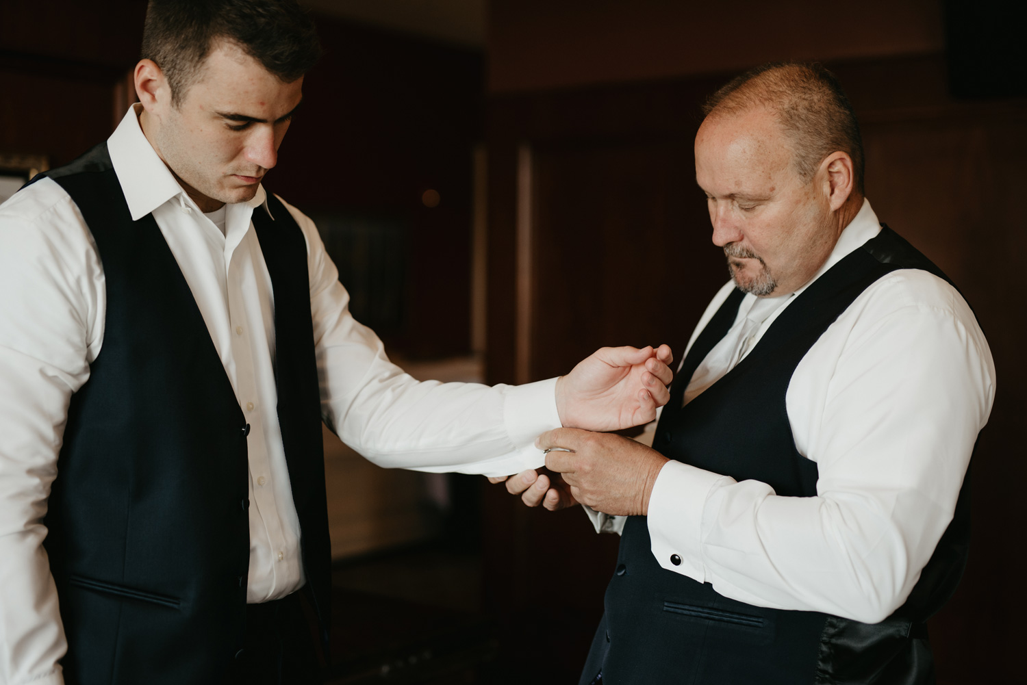Groom getting ready with dad buttoning up sleeves