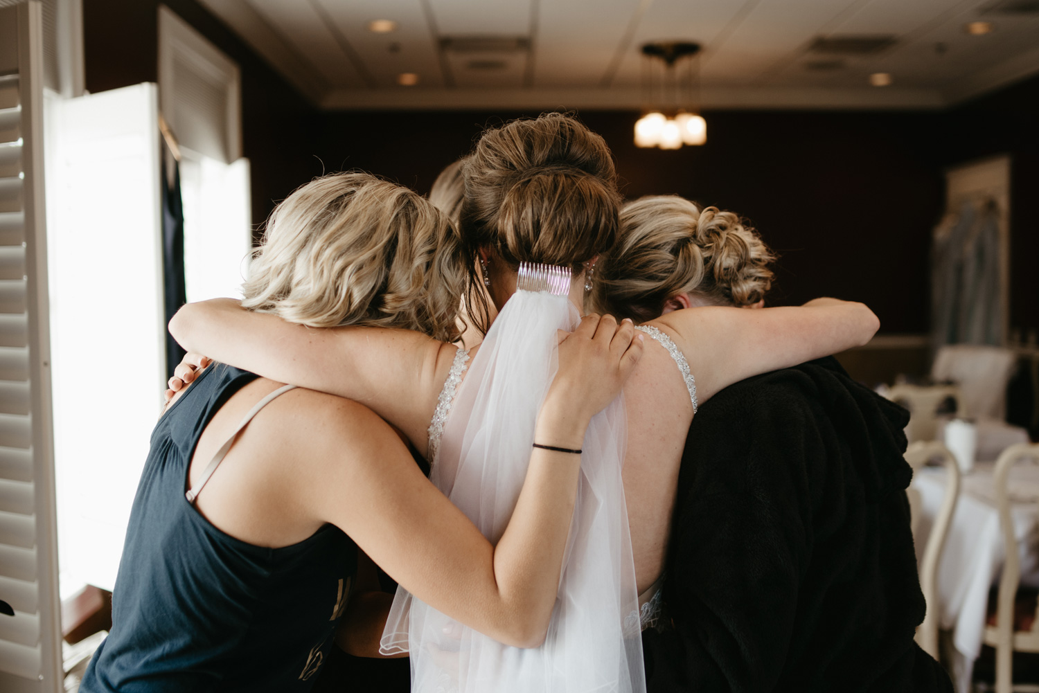 Bride hugging bridesmaids and veil falling out