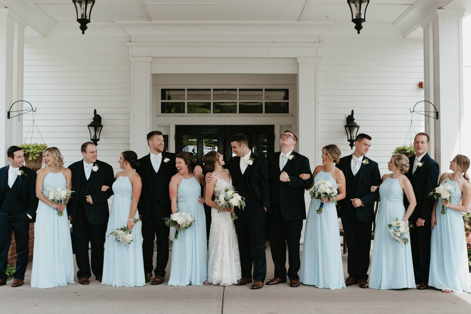 Bride, groom, and bridal party laughing together