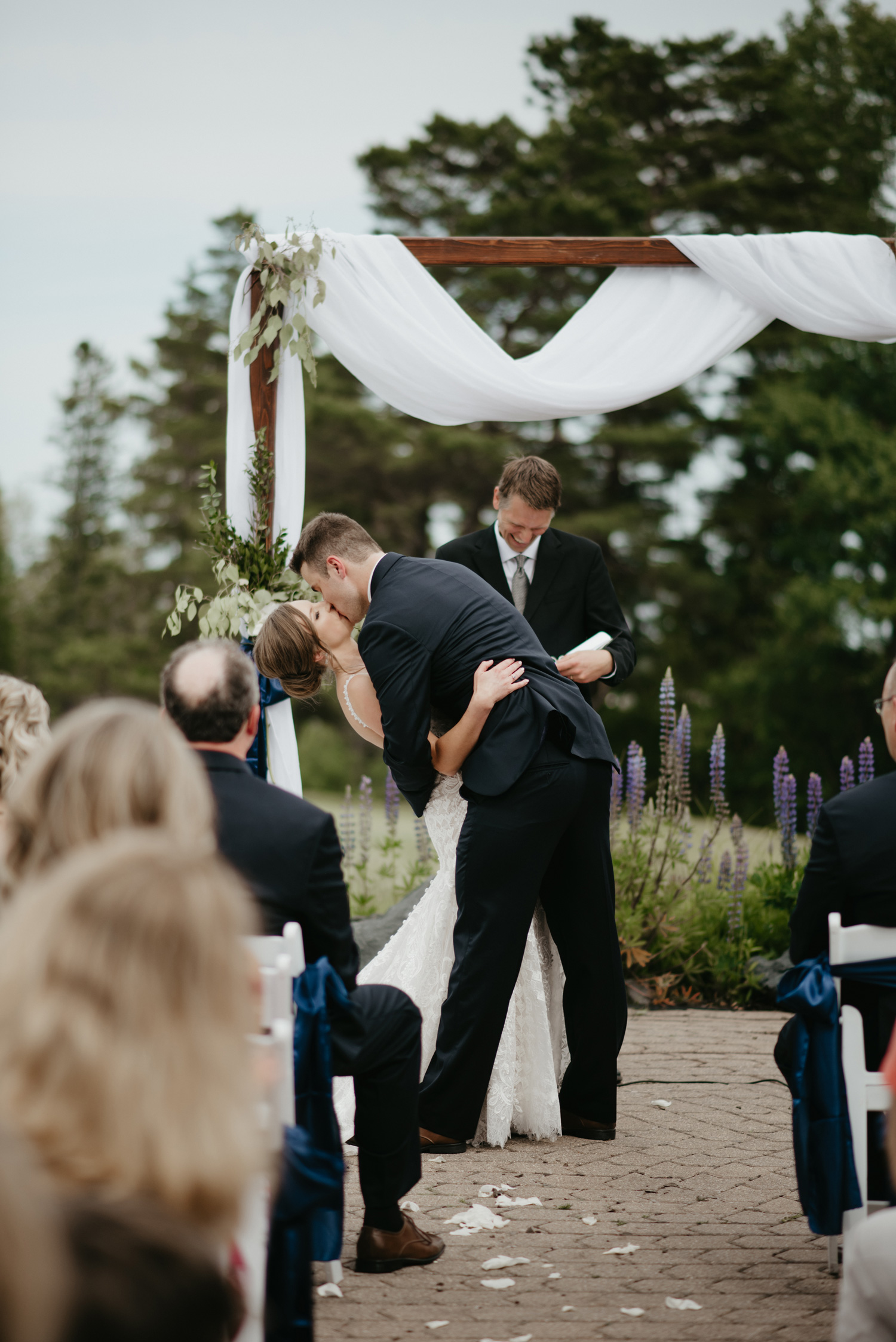 Bride and groom first kiss during outdoor ceremony
