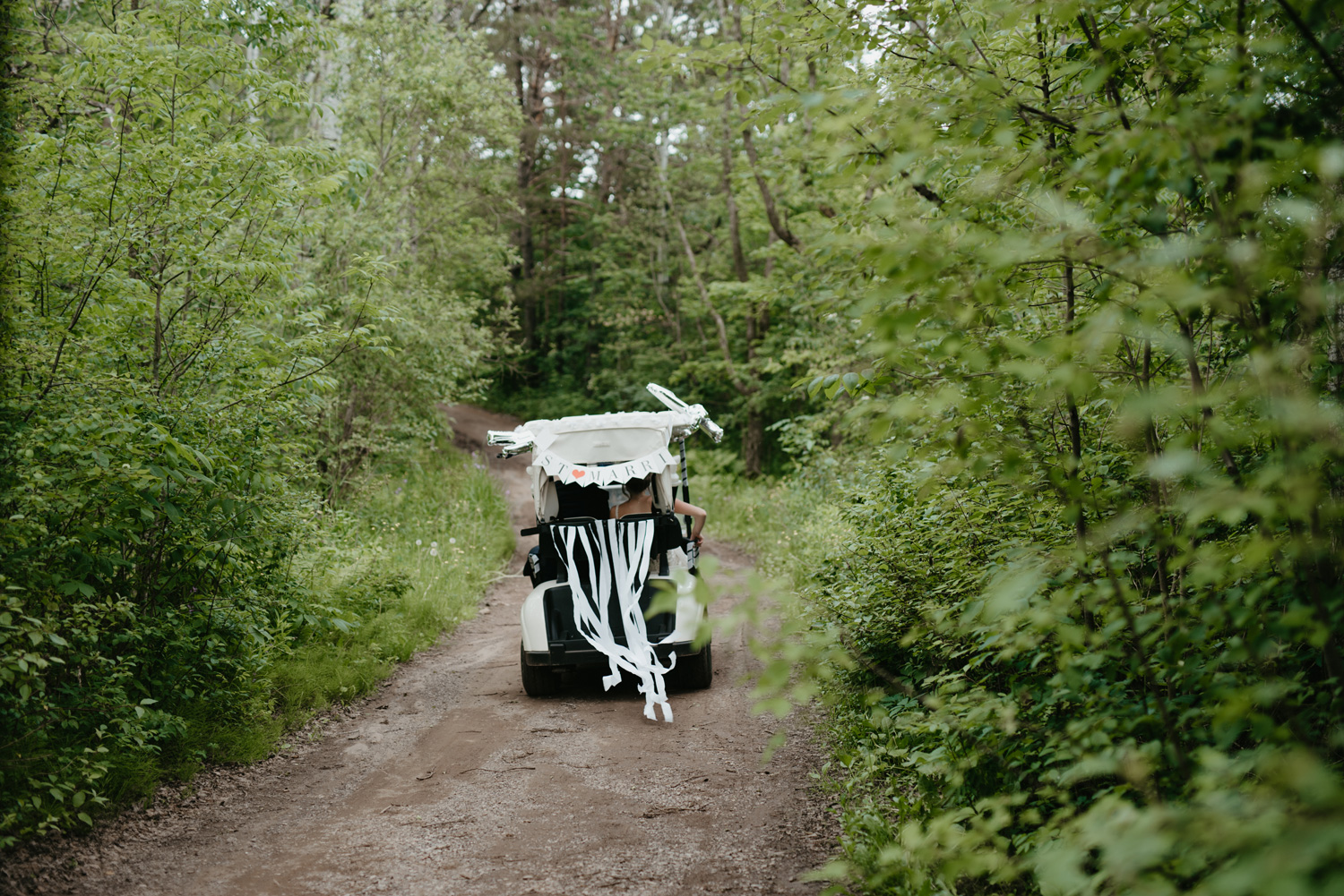 Bride and groom in getaway golf cart driving through woods