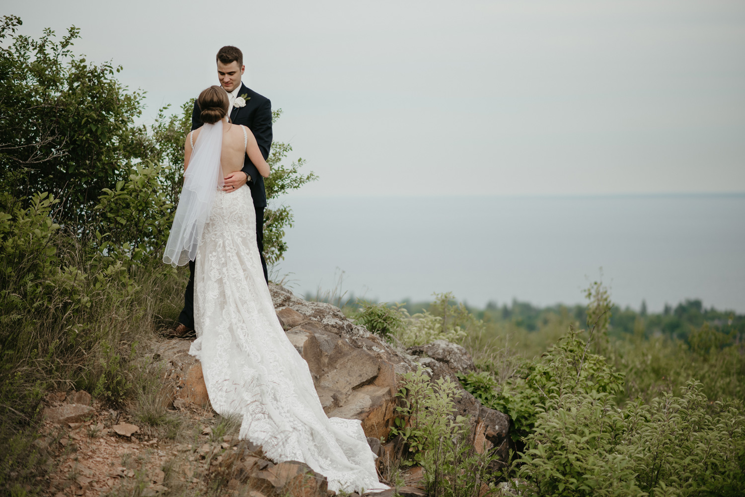 Bride and groom on rocks overlooking Lake Superior