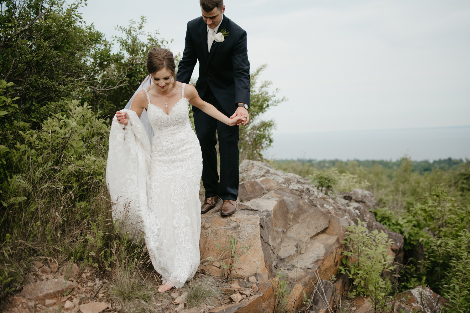 Bride and groom climbing rocks in North Shore Minnesota