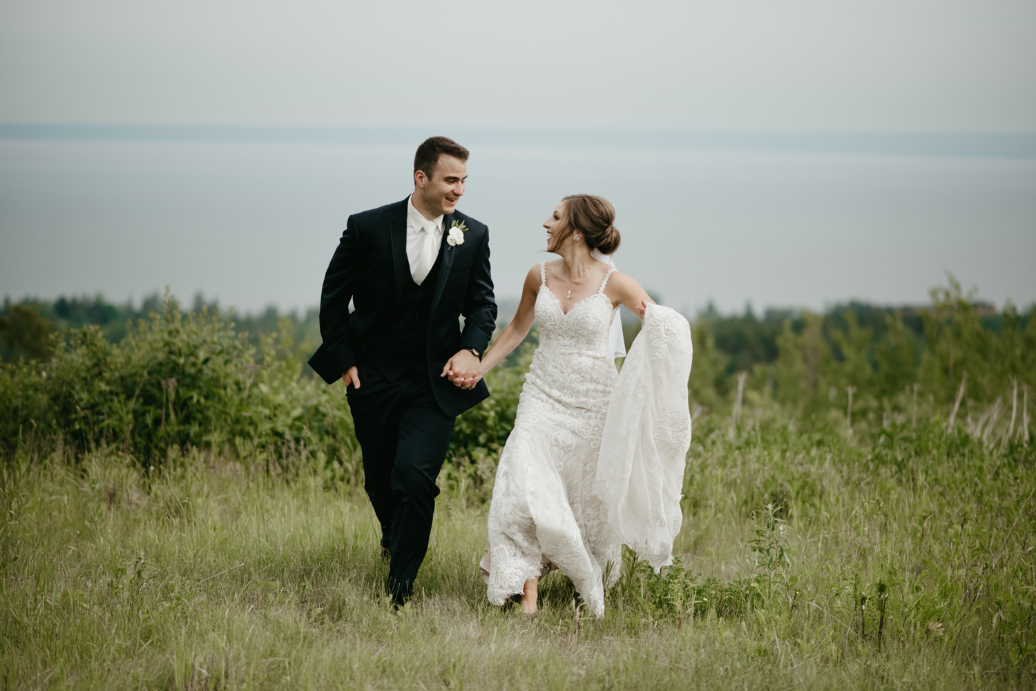 Bride and groom running together in a field