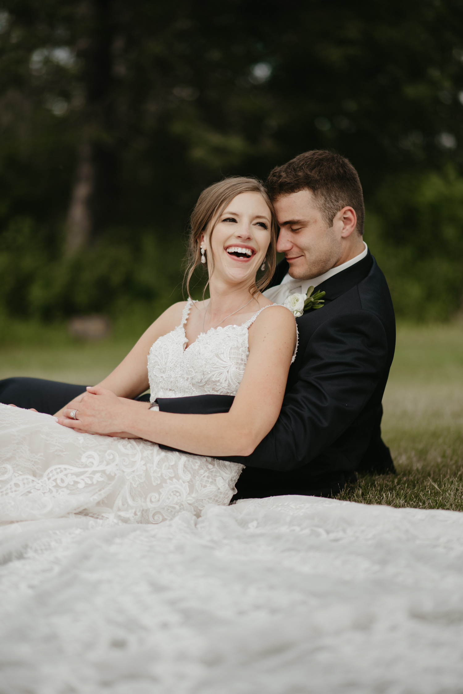 Bride and groom laughing laying down on grass