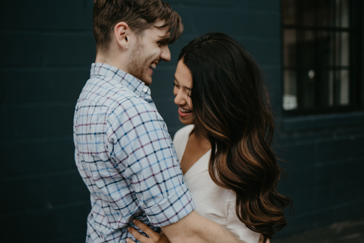 Man and woman cuddling and laughing in front of grey cinderblock wall