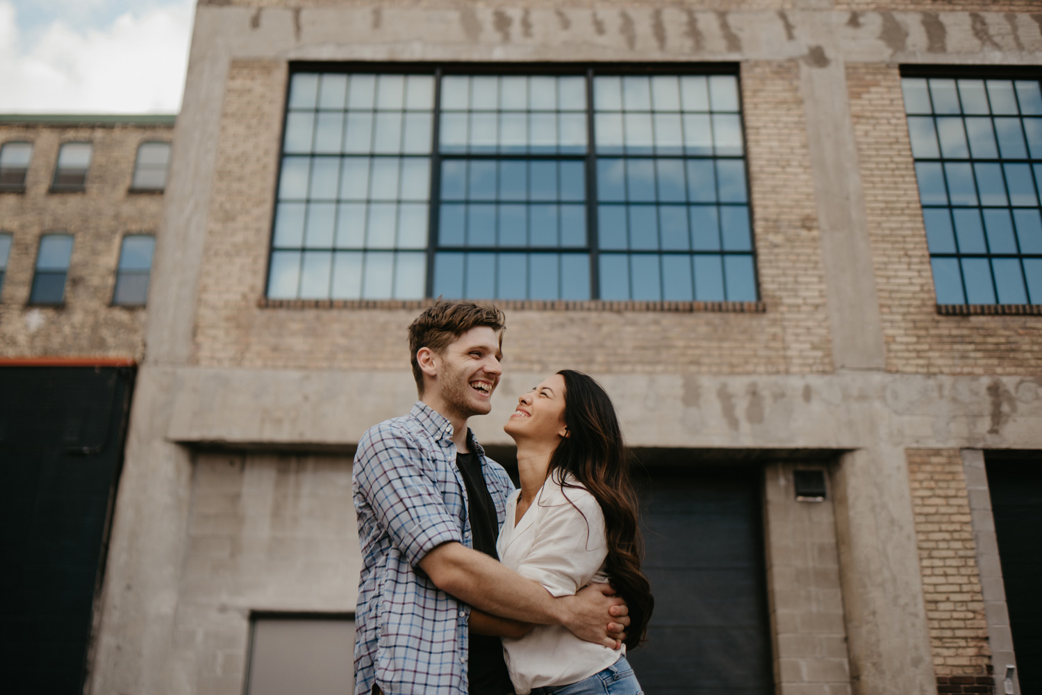 Man and woman cuddling in front of large urban warehouse with glass windows