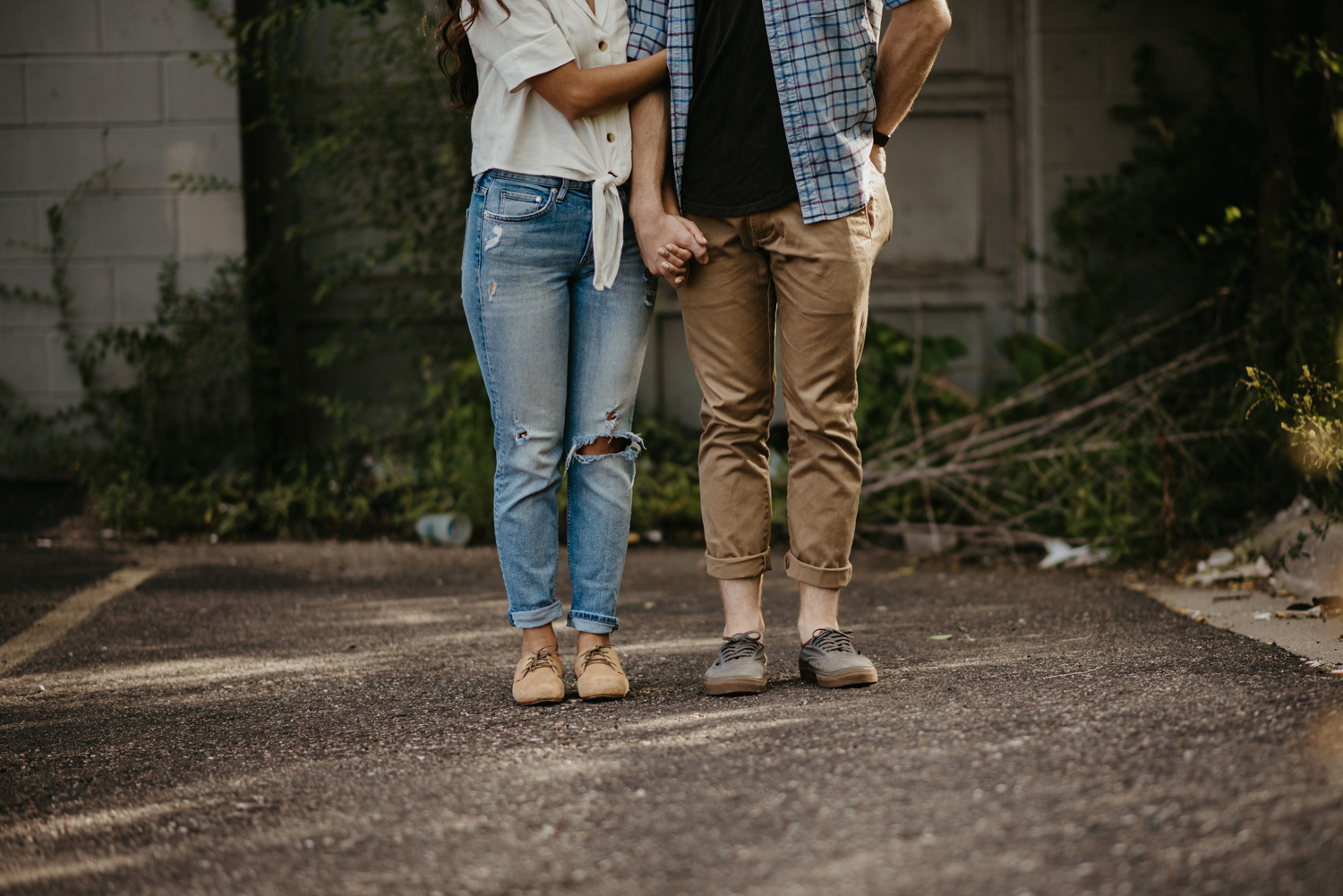 Torso and legs on man and woman in engagement photos standing side by side